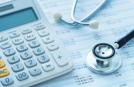 Calculator and stethascope on medical bills